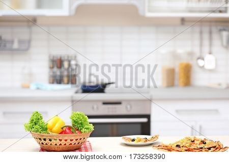 Vegetables and tasty pizza on kitchen table