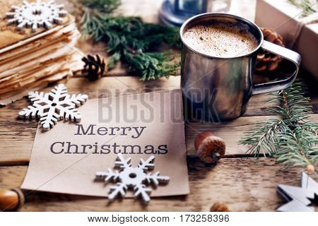 Cup of cocoa with greeting card on wooden background