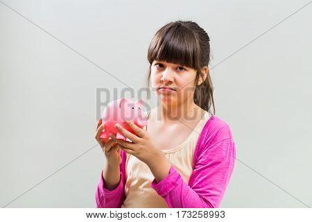 Photo of sad little girl holding piggy bank .