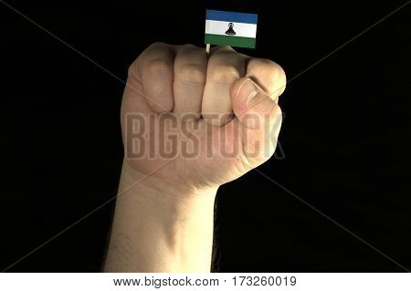 Man Hand Fist With Lesotho Flag Isolated On Black Background