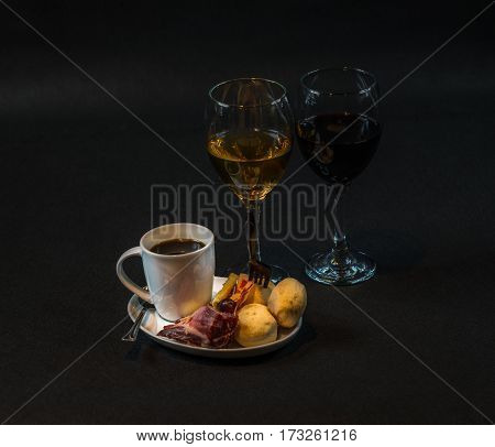 small snack consisting of meat and sausages French cheeses fresh crunchy bread black coffee red and white wine tasty snack