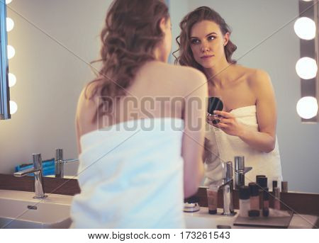 Young woman looking in the mirror and putting make-up on