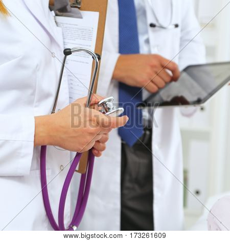 Doctor man showing something woman on tablet pc in hospital