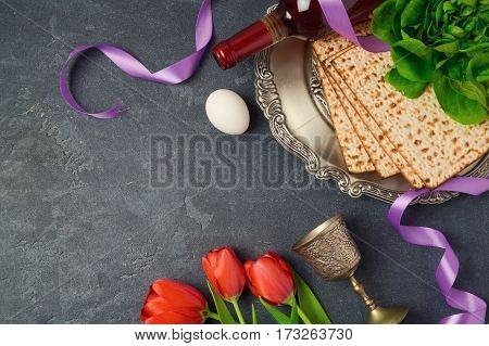 Passover holiday concept seder plate matzoh and tulip flowers on dark background. Top view from above