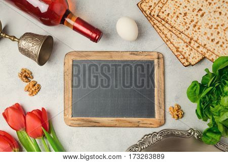 Passover holiday concept seder plate matzoh and chalkboard on bright background. Top view from above