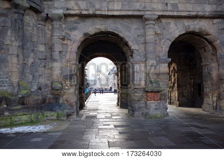TrierGermany- January 03 2017: Porta Nigra (Black Gate) - the biggest and most well-preserved ancient gates worldwide.Not far walking tourists
