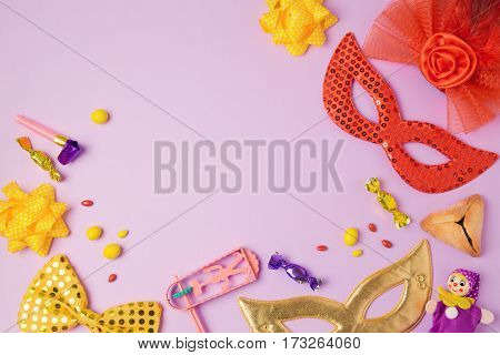 Purim holiday concept with carnival mask and party supplies on purple background. Top view from above. Flat lay