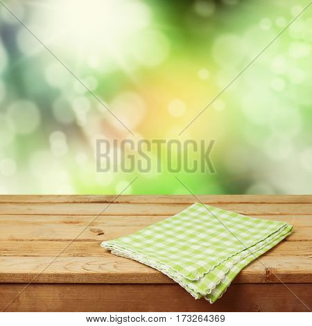Empty wooden deck table with checked tablecloth over nature bokeh background for product montage display