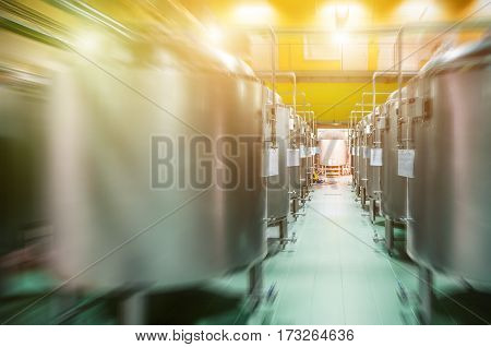 Modern Beer Factory. Rows of steel tanks for the storage and fermentation of beer. Spot light and motion blur effect