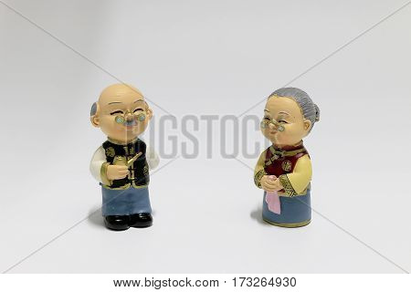 Two Dolls Which Made Like Grand Mom & Grand Dad In Chinese Uniform Style Standing On White Backgroun