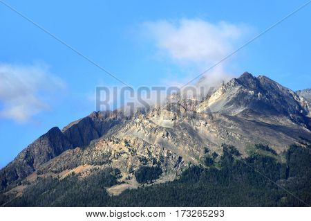 The rugged Immigrant Peak in Montana is surrounded by blue skies and whispy clouds. poster