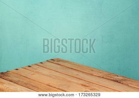 Empty wooden corner table over mint wall background for product montage display