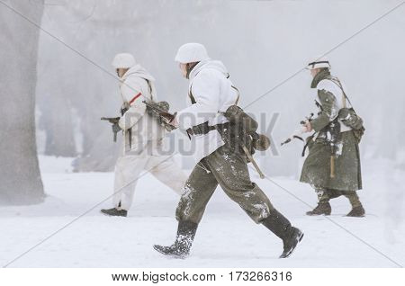 The park Ekaterinhof St. Petersburg (Russia) - February 23 2017: Military historical reconstruction of events of World War II. German soldiers with weapons at the ready in the snowy haze fleeing the attack.