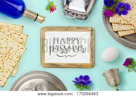 Passover holiday concept with wine bottle matzoh and photo frame over mint background. Top view from above