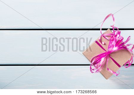 Gift box with nice pink ribbon on blue wooden background. Free space for text.