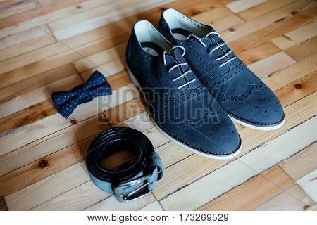 Wedding shoes belt and bowtie on a wooden background. Wedding accessories for the groom. Groom clothes.