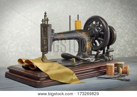 Vintage sewing machine with scissors, threads and cloth