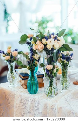 Сream and blue flowers in vases on a table with a lace tablecloth. Wedding decorations.