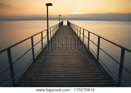 Wooden Footbridge into the lake of constance during a golgen sunset, germany