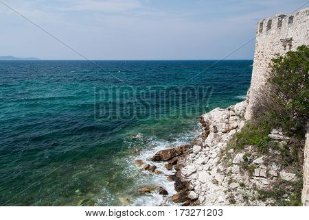 Ancient stone fortress wall on the edge of the Mediterranean sea with waves hitting large stones at the bottom of the cliff