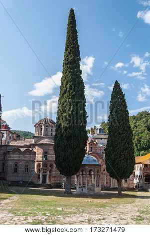 Ancient orthodox monastery courtyard with two cypress trees in front, Mount Athos, Greece