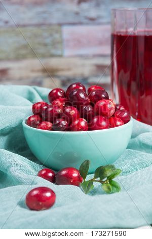 Red cranberry juice in a glass cranberries in the green clay bowl on the table