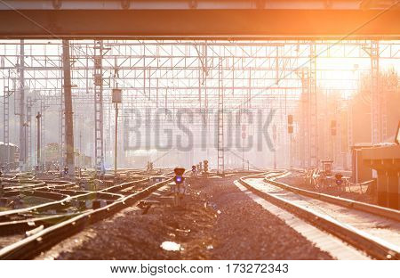 Perspective view of railway tracks with evening sun on the background
