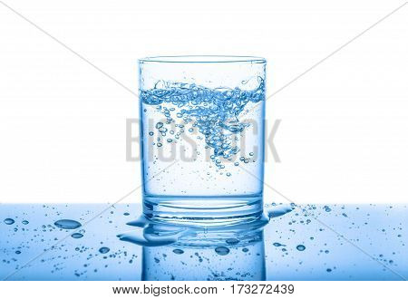 Water In Transparent Glass With Drops And Bubbles Isolated Over White, Blue Background, Close Up