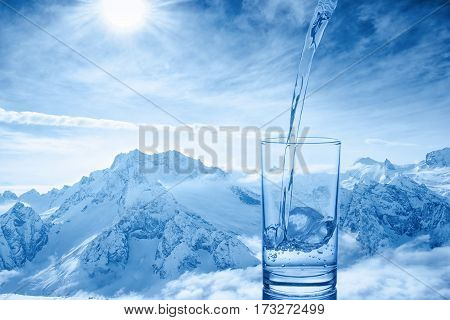 Beautiful Background Of Pouring Blue Water In Transparent Glass Over Winter Landscape Of Mountains H