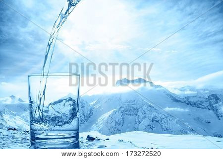 Concept Purity Of Blue Water In Transparent Glass Over Winter Landscape Of Mountains Higher Than Clo