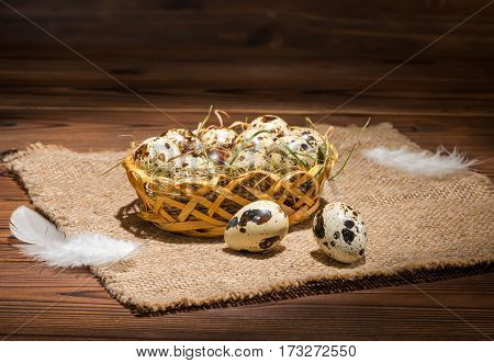 Quail Eggs With Straw And Feathers In Basket On Sackcloth Wooden Background, Rustic Style, Close Up