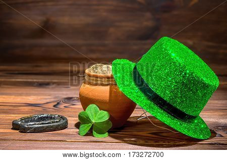 St Patricks Day Concept With Pot Full Gold Coins, Horseshoe, Green Hat And Shamrock On Vintage Woode
