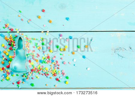 Easter background with cookie cutter in shape of symbol of Easter - Bunny and sugar sprinkles for cookies and cakes top view copy space