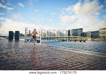 Shirtless Young Man Running Down Rainy Street