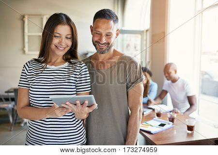 Female Showing Touch Pad To Male Co-worker