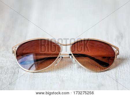 Stylish sunglasses on wooden background, closeup