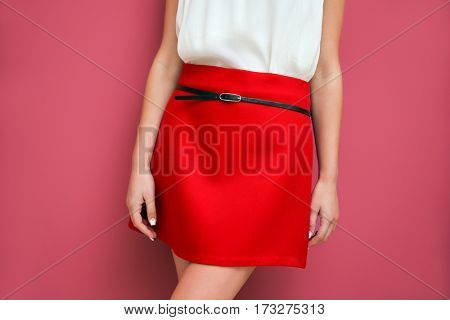 Woman in red skirt posing on color background