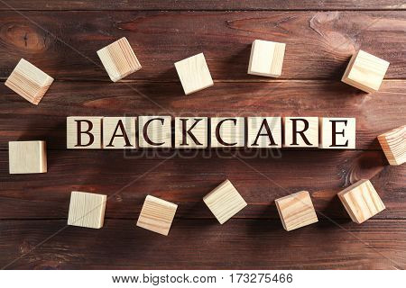Cubes with word POSTURE on brown wooden background