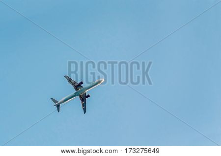 The plane flies against a bright cloudless blue sky.