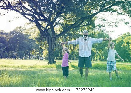 Grandfather Enjoy Grandchildren Outdoors Together