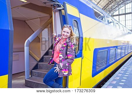 Young native dutch woman getting on a train in Amsterdam the Netherlands