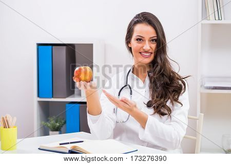 Beautiful female doctor showing apple while working at her office.