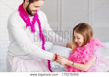 My sunny. Happy bearded male wearing white sweater and pink feather shawl putting his left hand on the shoulder of his daughter, standing in semi position