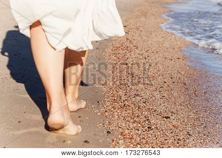 vacation travel - woman leg closeup walking on white sand relaxing in beach cover-up pareo beachwear. Sexy and tanned legs. Sunmmer holidays, weight loss or epilation, pedicure concept.