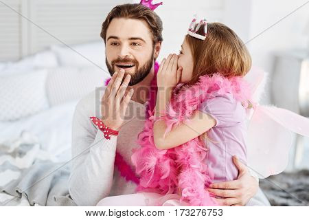 It is our secret. Young handsome man hugging his daughter keeping his right hand near his mouth while listening tales