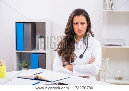 Angry female doctor sitting at her office thinking about something.