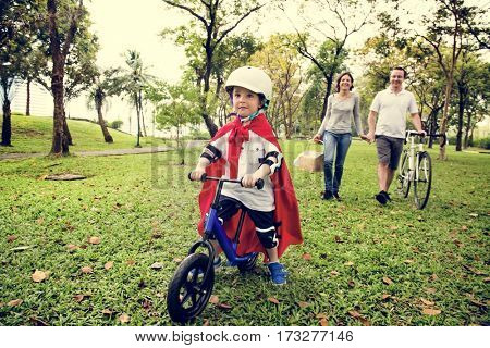Superhero little boy riding bicycle with family in the park