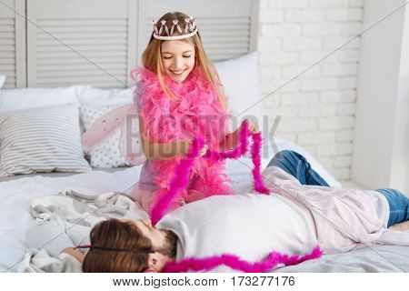 Play with me. Little princess wearing crown and pink shawl having smile on her face while looking at her father
