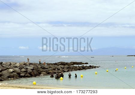 Los Cristianos beach Tenerife Canary Islands Spain Europe - June 13 2016: Scuba divers in the sea getting ready to dive