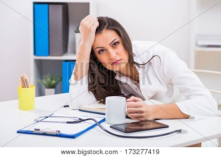 Tired female doctor is drinking coffee while working at her office.